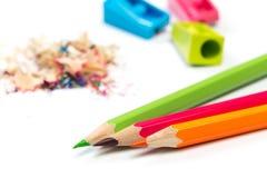 Farbige Bleistifte und Schnitzel mit Bleistiften Bleistiftspitzer von Bleistiften auf einem weißen Hintergrund lizenzfreies stockbild