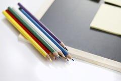 Farbige Bleistifte und schwarzes Brett Lizenzfreie Stockfotos