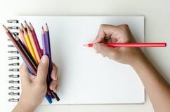 Farbige Bleistifte und Skizzieren des Mannes Holding Stockfotos