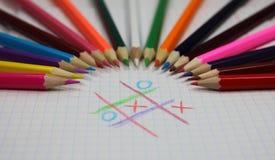 Farbige Bleistifte und Spielkreuze und -null Stockfotos