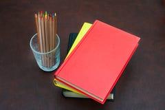 Farbige Bleistifte und Stapel von Büchern auf dem hölzernen Desktop Lizenzfreie Stockfotografie