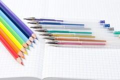Farbige Bleistifte und Stift und ein Notizbuch Lizenzfreies Stockfoto