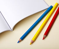 Farbige Bleistifte und unbelegtes Buch Lizenzfreie Stockbilder