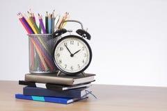 Farbige Bleistifte und Wecker, die auf Büchern steht Stockfotos