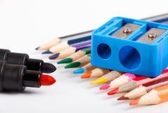 Farbige Bleistifte und zensieren Bleistiftspitzer auf weißem Hintergrund Lizenzfreie Stockfotografie