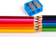 Farbige Bleistifte und zensieren Bleistiftspitzer auf weißem Hintergrund Stockbilder