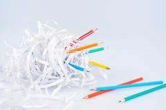 Farbige Bleistifte und zerrissene Papierkugel über Leuchte Stockbilder