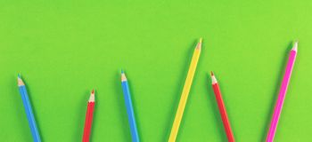 Farbige Bleistifte vereinbart auf Grünhintergrund Lizenzfreies Stockfoto