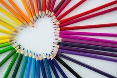 Farbige Bleistifte vereinbarten in der Herzform auf weißem Hintergrund Lizenzfreies Stockbild