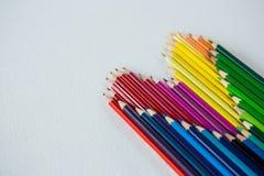 Farbige Bleistifte vereinbarten in der Herzform auf weißem Hintergrund Lizenzfreie Stockfotografie