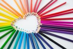 Farbige Bleistifte vereinbarten in der Herzform auf weißem Hintergrund Stockfotografie