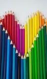 Farbige Bleistifte vereinbarten in der Herzform auf weißem Hintergrund Stockbild