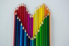Farbige Bleistifte vereinbarten in der Herzform auf weißem Hintergrund Lizenzfreie Stockbilder