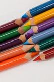 Farbige Bleistifte vereinbarten im Verriegelungsmuster auf weißem Hintergrund Lizenzfreies Stockfoto