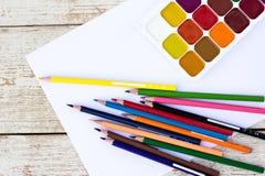 Farbige Bleistifte, Wasserfarben und Papier Lizenzfreie Stockfotografie