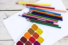 Farbige Bleistifte, Wasserfarben und Papier Lizenzfreies Stockfoto