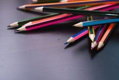 Farbige Bleistifte zerstreut auf den Schreibtisch Stockfotografie