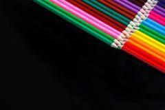 Farbige Bleistiftlüge gegenüber von lokalisiert auf dem schwarzen Hintergrund Lizenzfreie Stockfotos