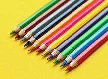Farbige Bleistiftpastelle auf einem Farbhintergrund lokalisiert Lizenzfreie Stockfotos
