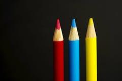 Farbige Bleistiftprimärzeichenstifte auf einem schwarzen Hintergrund Lizenzfreie Stockfotos