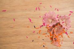 Farbige Bleistiftschnitzel auf einem hölzernen Hintergrund Lizenzfreie Stockfotos