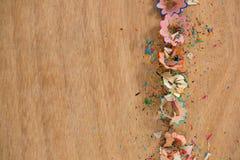 Farbige Bleistiftschnitzel auf hölzernem Hintergrund Stockbilder