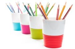 Farbige Bleistiftzeichenstifte in den bunten Behältern Lizenzfreie Stockfotos