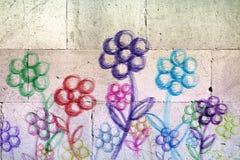 Farbige Blumen gezeichnet auf eine weiße Steinwand lizenzfreie stockfotografie