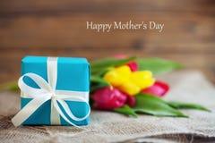 Farbige Blumenstraußtulpen und -geschenk für die Mutter Hintergrund E lizenzfreie stockfotografie