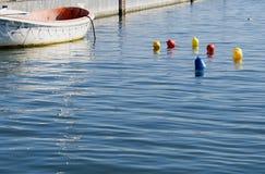 Farbige Bojen, die auf die Oberfläche im Hafen schwimmen Lizenzfreie Stockfotografie