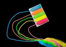 farbige Bookmarks, die zu einem Notizbuch oder zu einem Buch befestigt werden, lokalisiert auf einem schwarzen Hintergrund stockbilder