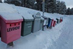 Farbige Briefkästen zeichnen bedeckt durch Schnee in Levi, Finnland Lizenzfreie Stockfotografie