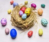 Farbige dekorative Eier für Ostern mit gemalten Gesichtern liegen in einem Draufsichtabschluß des Hintergrundes des Nestes hölzer Stockbild
