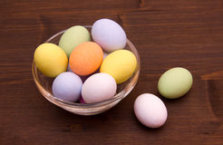 Farbige Eier auf Schüssel über Holz lizenzfreie stockfotografie