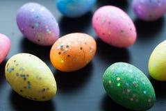 Farbige Eier auf schwarzem Hintergrund, Stockbild