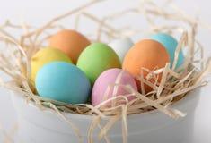 Farbige Eier in einem Strohnest Stockbilder