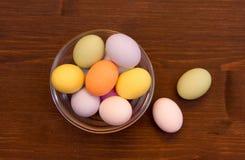 Farbige Eier innerhalb der Schüssel auf Holz von oben Stockfoto
