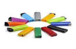 Farbige Feuerzeuge liegen in einem Kreis, der auf weißem Hintergrund lokalisiert wird Lizenzfreies Stockfoto