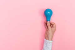 Farbige Glühlampe, die gehalten wird Lizenzfreie Stockfotografie