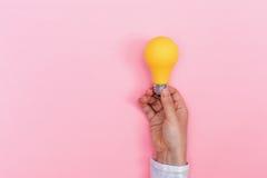 Farbige Glühlampe, die gehalten wird Lizenzfreie Stockfotos