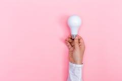 Farbige Glühlampe, die gehalten wird Lizenzfreie Stockbilder