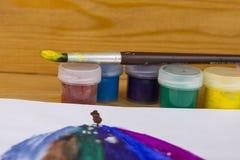 Farbige Gouachedosen auf hölzernem Hintergrund, malen für das Zeichnen Kindergarten und Schule Mehrfarbiger Lack Kind-` s Kreativ lizenzfreie abbildung
