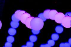 Farbige hängende Lichter der runden Kugel verschoben in den Reihen auf schwarzem Hintergrund lizenzfreie stockbilder