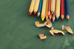 Farbige hölzerne Bleistifte gegen ein grünes Brett Lizenzfreie Stockfotografie