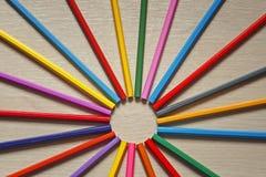 Farbige hölzerne Bleistifte sind auf dem Tisch herum als die Sonne Lizenzfreie Stockfotografie