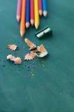 Farbige hölzerne Bleistifte und Bleistiftspitzer Stockfotografie