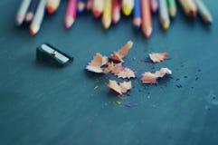 Farbige hölzerne Bleistifte und Bleistiftspitzer Stockfoto