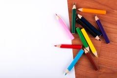 Farbige hölzerne Bleistifte verschüttet und Weißbuch auf Tabelle Stockfotografie