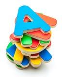 Farbige hölzerne Buchstaben, gestapelt Stockfotos