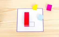 Farbige Holzklötze liegen nahe der Schablone, die wiederholt werden muss Farbige Holzklötze, Würfel, Gestalt auf einem hellen höl lizenzfreie stockfotografie